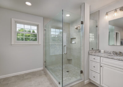 Woodbine, MD Primary Bath with Carrara marble accent tile, Cambria countertop, frameless shower glass, brushed nickel finishes.